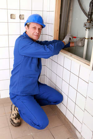 screwing: Plumbing screwing a pipe into a bracket