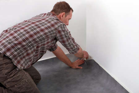 knelt: Man laying new carpet in room