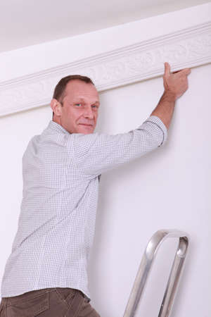 Smiling man fixing coving to a ceiling photo