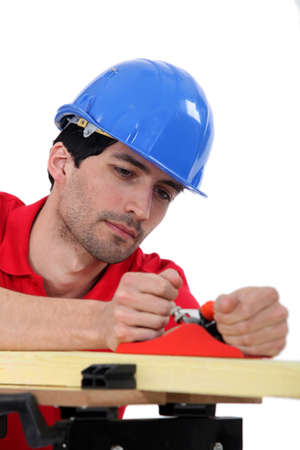 whittle: Carpenter with wood plane Stock Photo