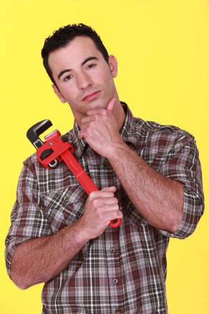 chew over: Workman holding a pipe wrench