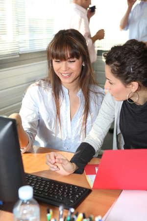 Mujer sonriendo y charlando en un escritorio de oficina