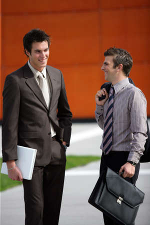 Two young businessmen sharing a joke Stock Photo - 12219407