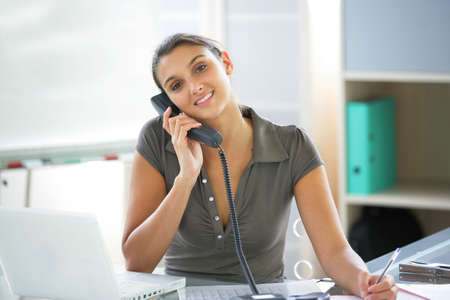 Young woman on the phone at her desk Stock Photo - 12219206