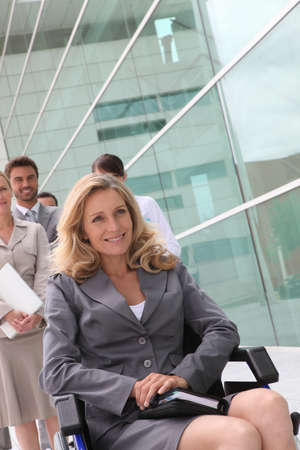 wheelchair woman: Businesswoman in a wheelchair with colleagues outside an office building
