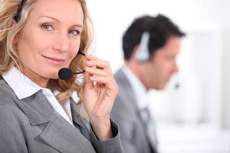 Woman in a suit using a headset with a male colleague in the background photo