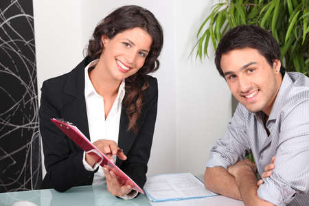 salesmen: Woman showing man where to sign Stock Photo