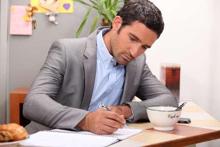 hombre escribiendo: Hombre de negocios que trabaja en su barra de desayuno