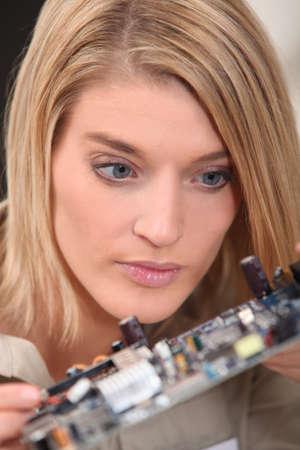 exactness: female technician watching an electronic circuit Stock Photo