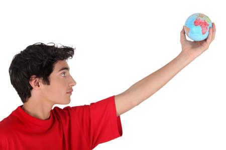 inclination: Boy holding a mini globe