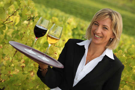 personable: Waitress with red and white wine in a vineyard Stock Photo