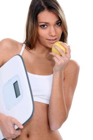 portrait of beautiful Latina eating apple with scales photo