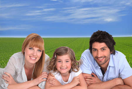 high spirited: couple with daughter lying cross-armed in green setting Stock Photo