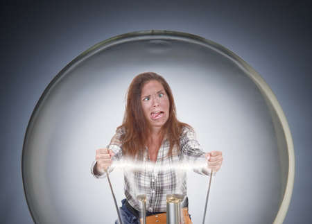 Woman in big light bulb being electrocuted photo