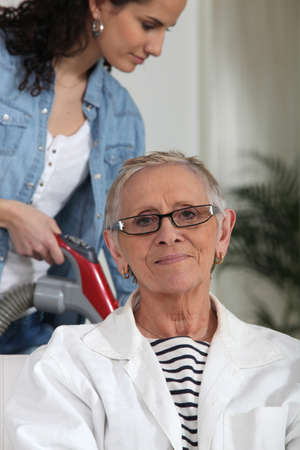Young woman helping an older lady with the housework photo