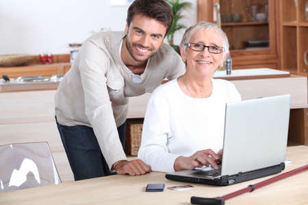 Young man helping senior woman with a laptop compute photo