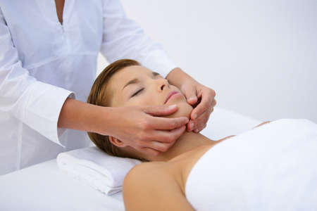 Woman being treated to face massage photo