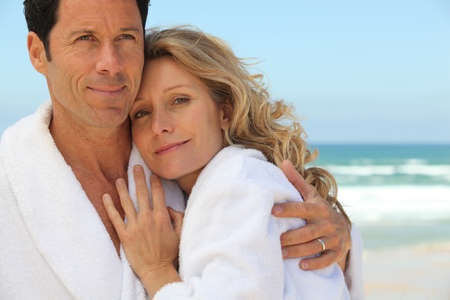 toweling: Couple embracing by the sea in toweling robes