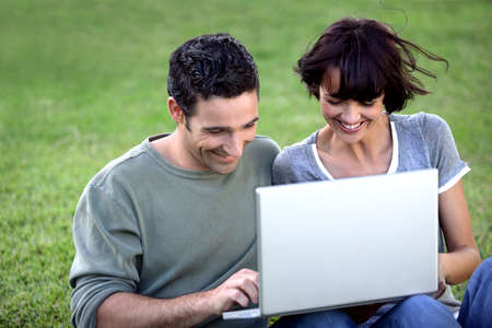 Couple sat with laptop in the park photo