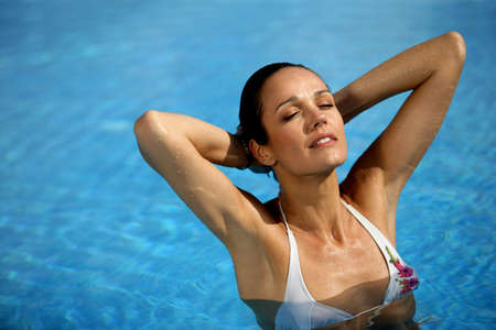 Brunette stood in pool wearing white bikini photo