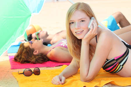 red head girl: a girl at phone and her friends leaning down on the beach
