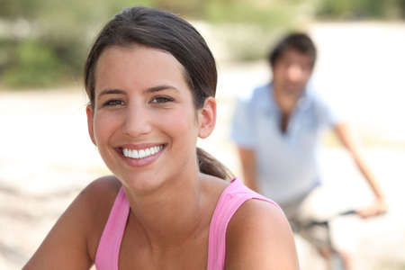 he she: woman smiling with a man biking in background