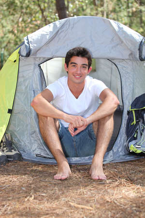 Teenage boy sitting in front of his tent on a sunny day photo