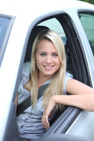 Young woman leaning out of car window photo
