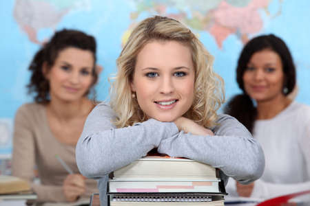 Three teenage girls in class room photo