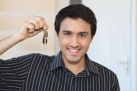Young man with a doorkey photo