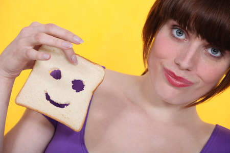 Woman with a smiley piece of bread Stock Photo - 12219228