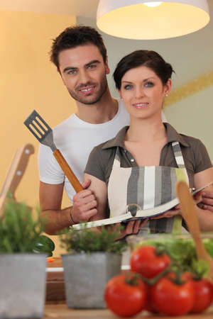 Couple in a kitchen with a cookbook photo