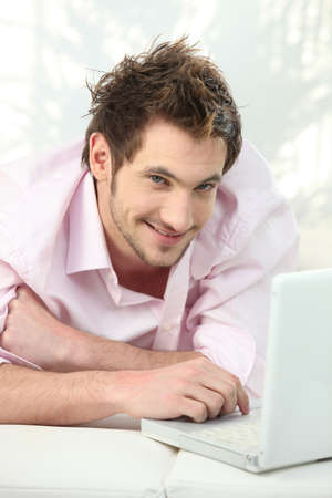 slumped: young man lying on couch using laptop Stock Photo