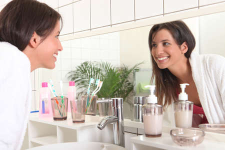 bathroom mirror: Woman looking in bathroom mirror Stock Photo
