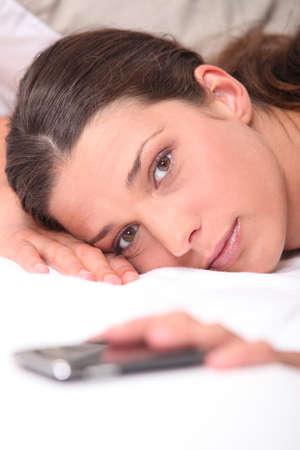 obudził: Zbliżenie kobieta w łóżku sięgając po telefon