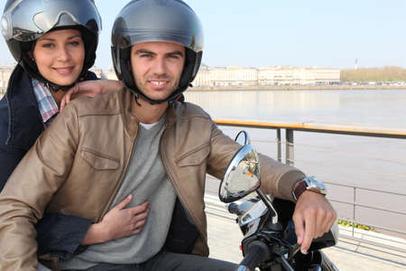 Young couple on a moped by a river photo