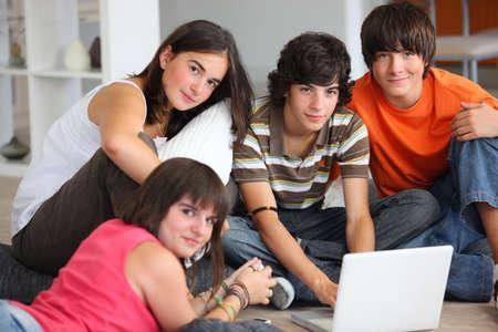 adolescentes estudiando: los adolescentes se divierten con un ordenador port�til en casa Foto de archivo