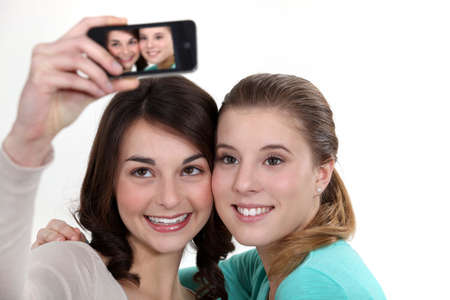 Girls taking picture with mobile phone photo