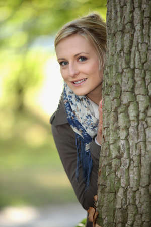 Blond stood behind tree Stock Photo
