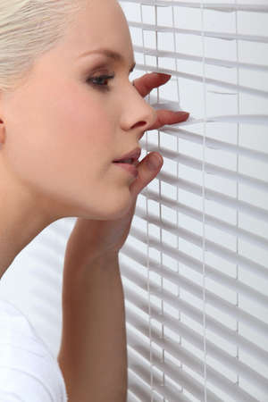 Blond woman peering through window blind photo