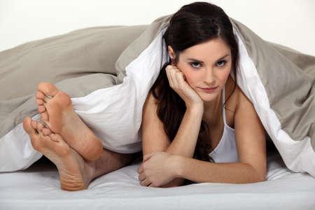 molesto: Molesta la mujer en la cama junto a su pareja Foto de archivo