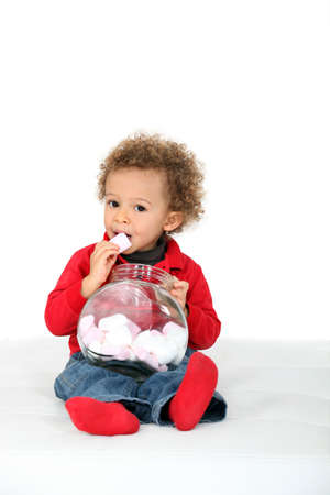 Young girl eating candies photo