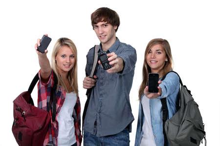 mobiele telefoons: Drie tieners studenten met rugzakken en mobiele telefoons Stockfoto
