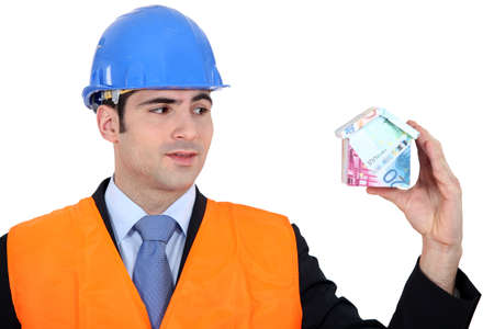 property development: Inspector with a house made of money Stock Photo