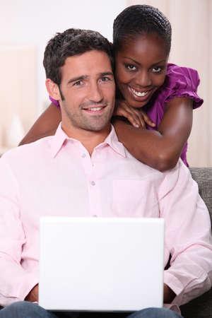 couple mixte: Couple mixte avec un ordinateur portable