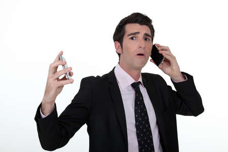 Overwhelmed businessman answering telephones photo
