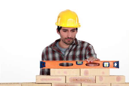 aligning: Mason checking level of a brick wall