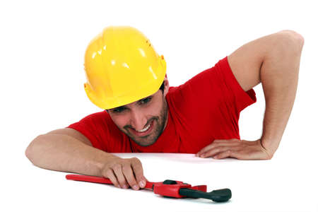 tradesperson: Man struggling to reach a pipe wrench Stock Photo