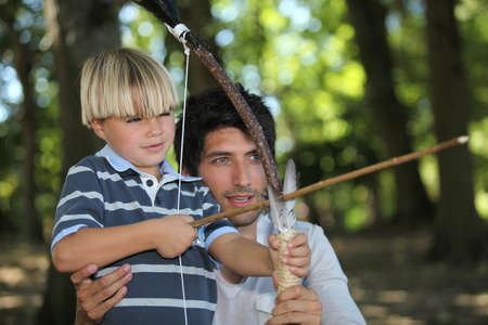 a man and a little boy doing archery in the forest photo