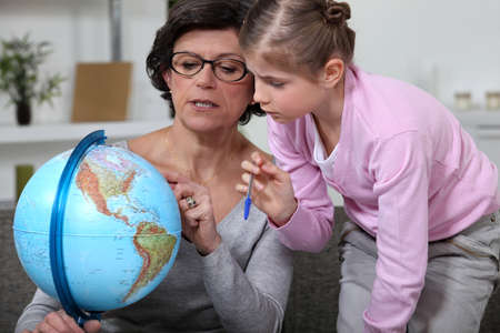 Little girl looking at a globe with her grandmother photo